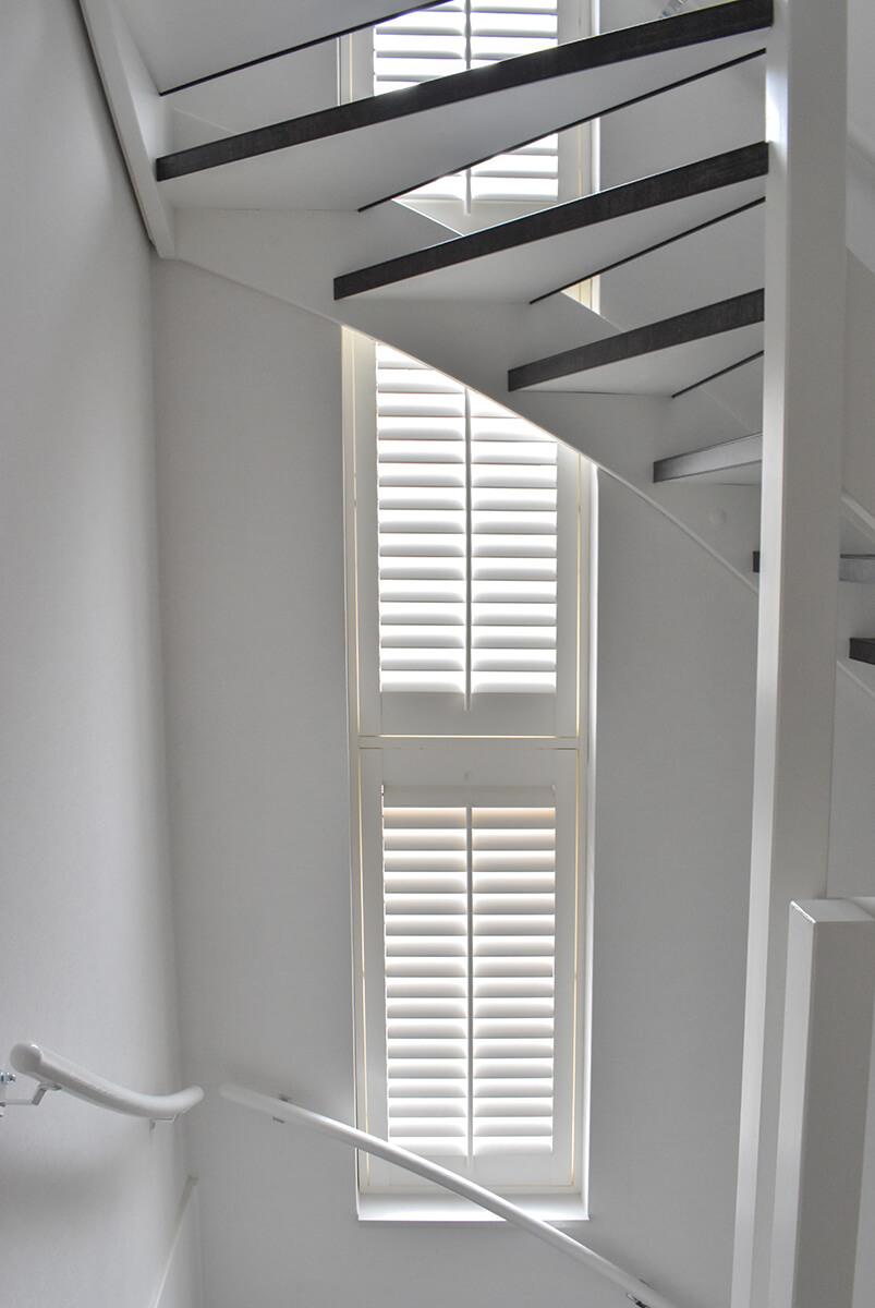 witte shutters smal raam trapgat